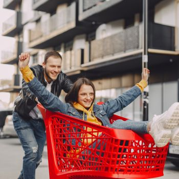 Canva - Man riding girl on shopping trolley on parking