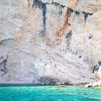 Canva - Person Swimming Near Brown Cliff