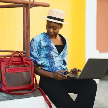 Canva - Woman Sitting Beside Bag And Using Laptop